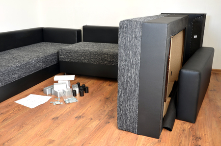floor cloth: Modern black and white cloth sofa assembly, assembling parts of sofa on brown wooden floor with paper instruction