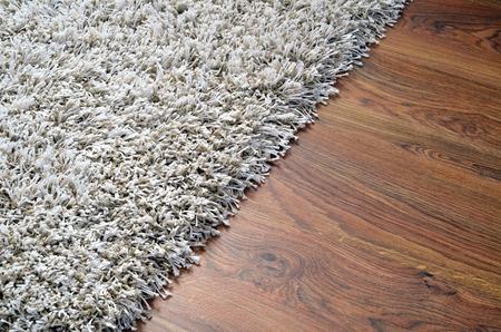 Witte shaggy tapijt op de vloer bruine houten detail