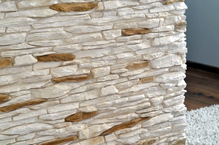 View into the living room through a wall tiled rough stone cladding photo