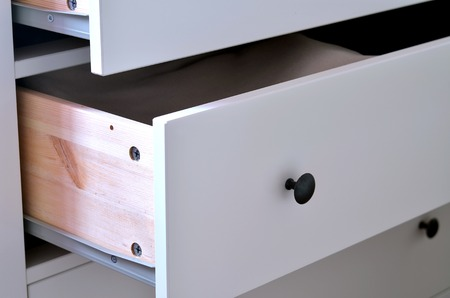 laminated: Detail of open white laminated drawer with brass handle