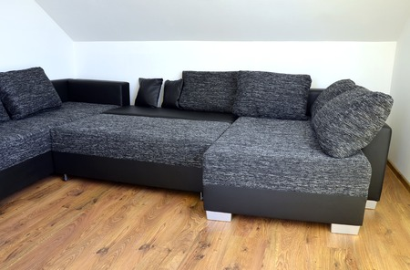 Modern black and white cloth sofa with black leather and pillows photo