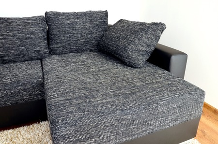 Modern black and white cloth sofa with black leather and pillows on shaggy carpet photo