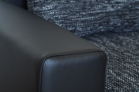 Detail of black leather armchair on black and white cloth sofa photo