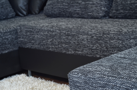 Closeup view to modern black and white cloth sofa with black leather, pillow and shaggy carpet photo