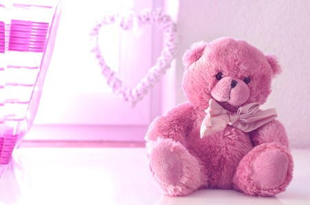 plushy: Romantic still life with pink plushy teddy bear in the foreground a pink curtain and heart in the background Stock Photo