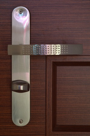 Front view to modern chrome handle with key on dark brown wooden door photo