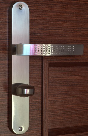 view of a wooden doorway: Modern chrome handle with key on dark brown wooden door