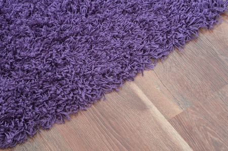 Purple shaggy carpet on brown wooden floor detail photo