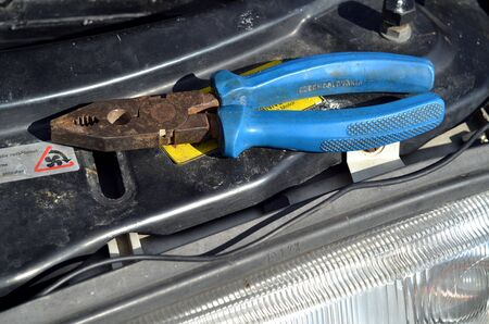 benzin: Repairing of modern car, detail to fixing car light and pliers