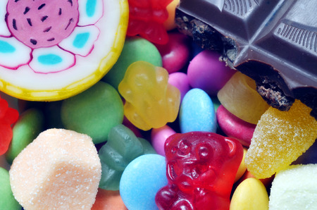 smarties: Macro detail of lollipop, gummy bears, chocolate and sour candy on colored smarties background