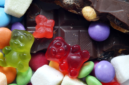 smarties: Macro detail of gummy bears, chocolate and sour candy on colored smarties background