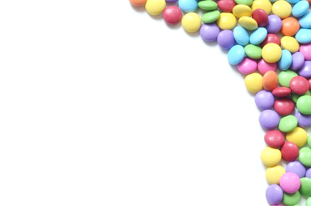 Isolated heap of colored smarties on white background shape like right frame