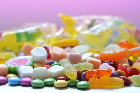 banque dimages candy sucette color smarties et les oursons de glatine au premier plan et forfaits de bonbons floues de fond rose - Sucette Colore