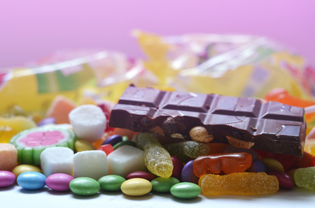 smarties: Candy, lollipop, colored smarties, chocolate and gummy bears in foreground and blurred candy packages in pink background