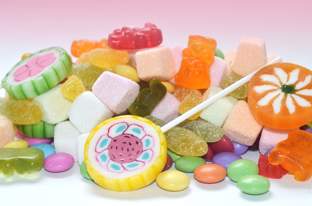 smarties: Candy, lollipop, colored smarties and gummy bears in foreground and blurred candy packages in pink background
