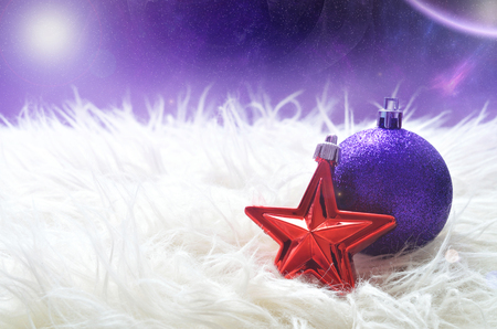 Sparkly purple christmas ball and red star lying on a white furry nest in foreground and magic starry space with nebula and planet in background photo