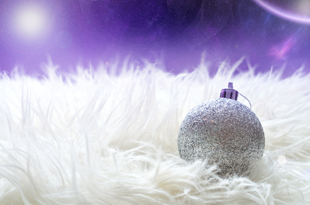 sparkly: Sparkly silver christmas ball lying on a white furry nest in foreground and magic starry space with nebula and planet in background Stock Photo