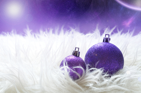 sparkly: Sparkly purple big and small christmas balls lying on a white furry nest in foreground and magic starry space with nebula and planet in background