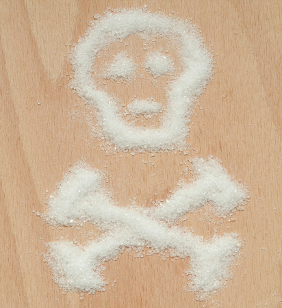 White crystal sugar spilled into the shape of a skull with crossed bones metaphorically symbolizing unhealthiness