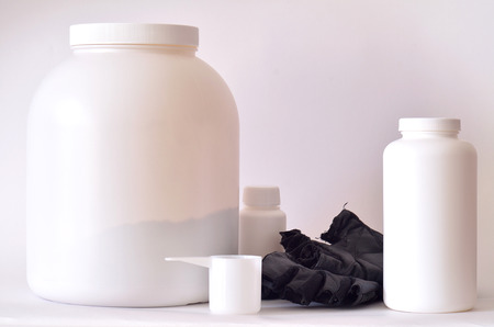 multivitamin: Big jar of protein powder, bottle of BCAA, multivitamin pills, fitness gloves and red shaker Stock Photo
