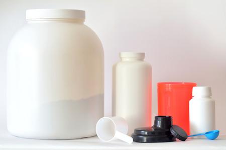 multivitamin: Big jar of protein powder, bottle of BCAA, multivitamin pills and shaker Stock Photo