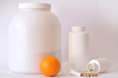 multivitamin: Big jar of protein powder, multivitamin pills, orange and scoop