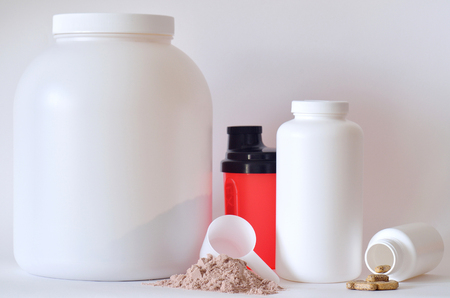 multivitamin: Big jar of protein powder, multivitamin pills, soluble magnesium tablets and shaker Stock Photo