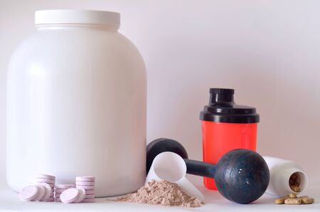 Big jar of protein powder, multivitamin pills, soluble magnesium tablets, orange shaker and dumbbell photo