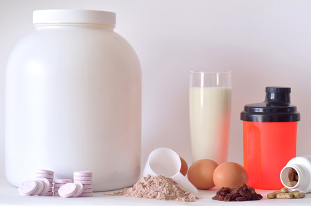 Big jar of protein powder, glass of milk, eggs, multivitamin pills, soluble magnesium tablets, raisins and red shaker photo