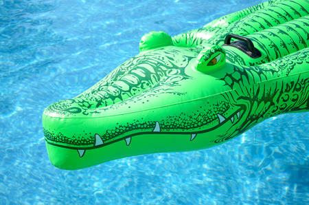 Inflatable deck chair in the shape of a crocodile in the pool Stock Photo