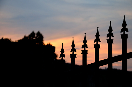 iron fence: Silhouette of forged gate on orange evening sunset sky