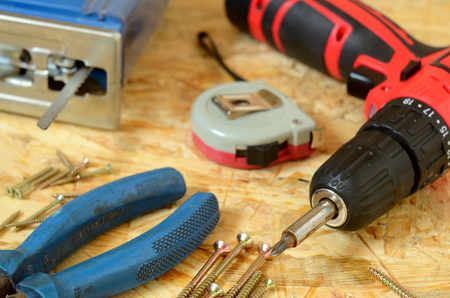drill floor: Set of tools - jigsaw, drill, pliers, screws and construction meter placed on OSB board Stock Photo