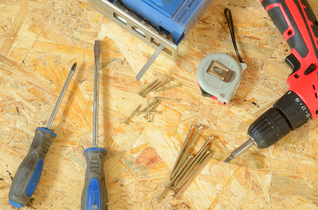 osb: Set of tools - jigsaw, drill, pliers, screws, screwdriver and construction meter placed on OSB board