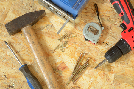 osb: Set of tools - jigsaw, drill, screws, hammer, screwdriver and construction meter placed on OSB board
