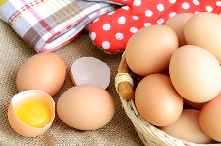 albumen: Wicker basket with eggs and broken raw egg with the yolk and albumen on a linen tablecloth
