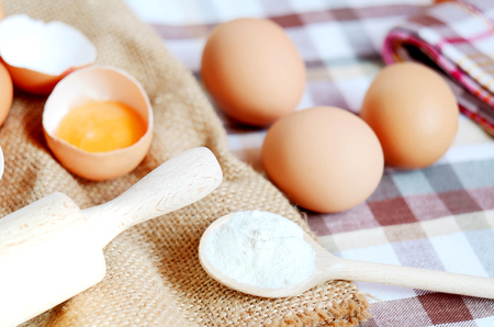 albumen: Eggs and broken raw egg with the yolk and albumen on a linen tablecloth