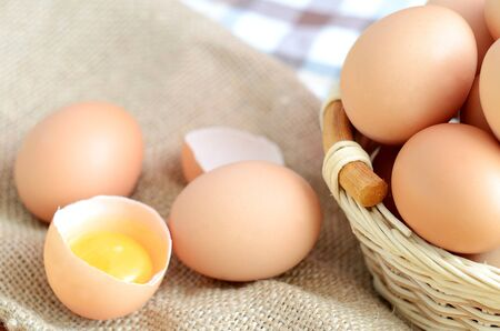 albumen: Wicker basket with eggs and broken raw egg with the yolk and albumen on a linen tablecloth with a striped dish towel Stock Photo