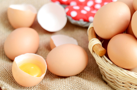 albumen: Wicker basket with eggs and broken raw egg with the yolk and albumen on a linen tablecloth with a striped dish towel and red potholder with white polka dots
