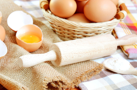 albumen: Wicker basket with eggs and broken raw egg with the yolk and albumen on a linen tablecloth with a striped dish towel, wooden rolling pin and wooden spoon with flour