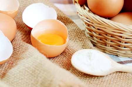 albumen: Wicker basket with eggs and broken raw egg with the yolk and albumen on a linen tablecloth with a striped dish towel and wooden spoon with flour Stock Photo