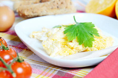 breadboard: Breakfast, scrambled eggs on a square plate, toast bread, cherry tomatoes and a wooden breadboard on a green tablecloth
