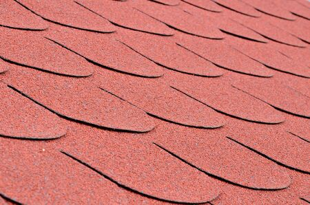 asphalt shingles: Close up detail of red shingles on a roof