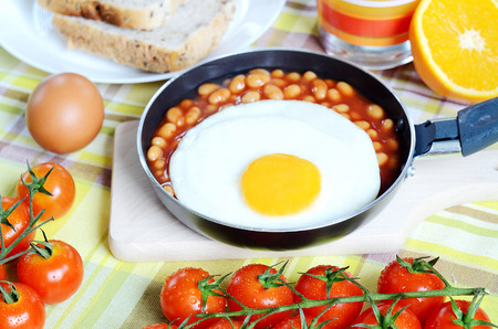 beans on toast: Breakfast, fried egg with beans in a frying pan, toast bread, fresh orange juice, tomatoes and a wooden breadboard on a green tablecloth