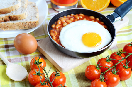 beans on toast: Breakfast, fried egg with beans in a frying pan, toast bread, fresh orange juice, tomatoes and a wooden breadboard, spoon on a green tablecloth Stock Photo