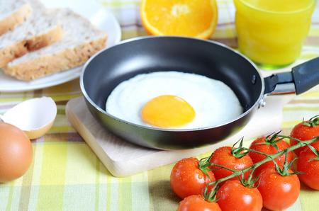breadboard: Breakfast, fried egg in a frying pan, toast bread, fresh orange juice, tomatoes and a wooden breadboard on a green tablecloth