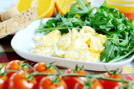 breadboard: Breakfast, scrambled eggs on a square plate with arugula, toast bread, fresh orange juice, cherry tomatoes and a wooden breadboard on a green tablecloth