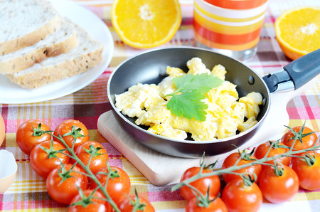 breadboard: Breakfast, scrambled eggs in a frying pan, toast bread, fresh orange juice, cherry tomatoes and a wooden breadboard on a green tablecloth Stock Photo