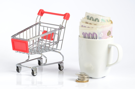 czech republic coin: Shopping cart and czech coins and banknotes money currency in white cup symbolizing saving money isolated on white background