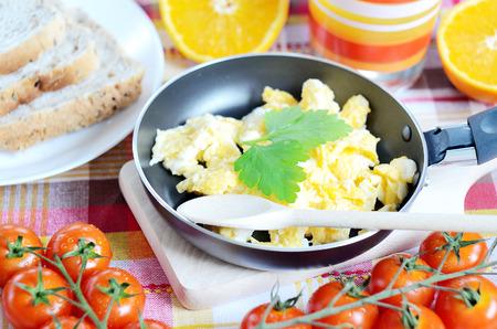 breadboard: Breakfast, scrambled eggs in a frying pan, toast bread, fresh orange juice, cherry tomatoes and a wooden breadboard, spoon on a green tablecloth