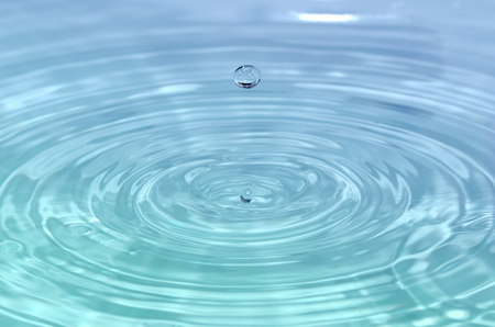 circular blue water ripple: Beautiful close up detail of a splashing water drop in blue - turquoise water Stock Photo